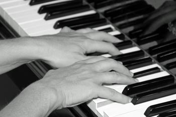 Hands on piano black and white